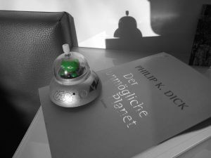 UFO-Spielzeug auf der Science-Fiction-Anthologie 'Der unmögliche Planet' von Philip K. Dick
