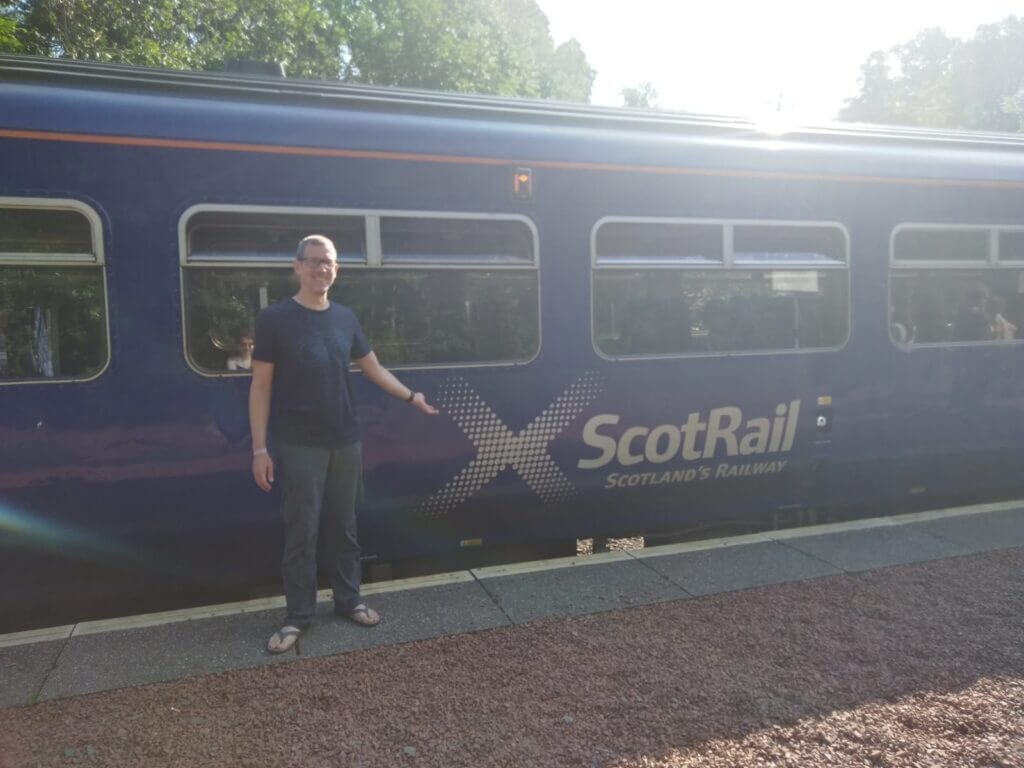 Ingo Steinke in front of a blue train with the ScotRail logo at a sunny station in the Scottish Higlands.