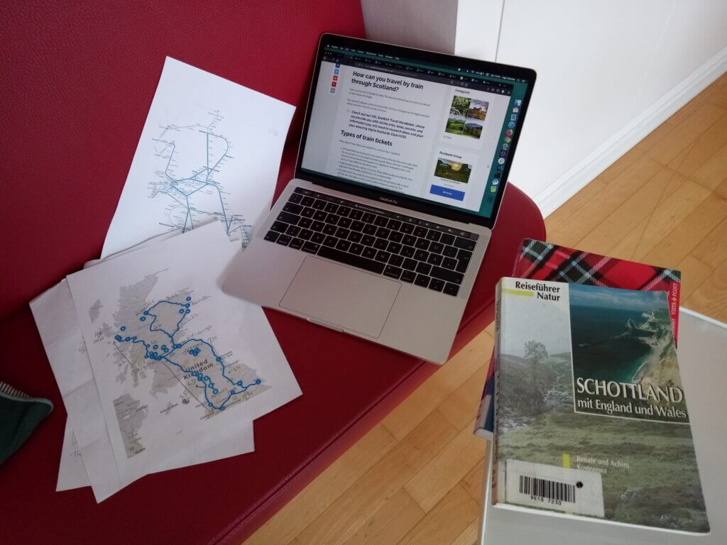 Laptop, sheets of paper and books on a red bench, all with information about Scotland