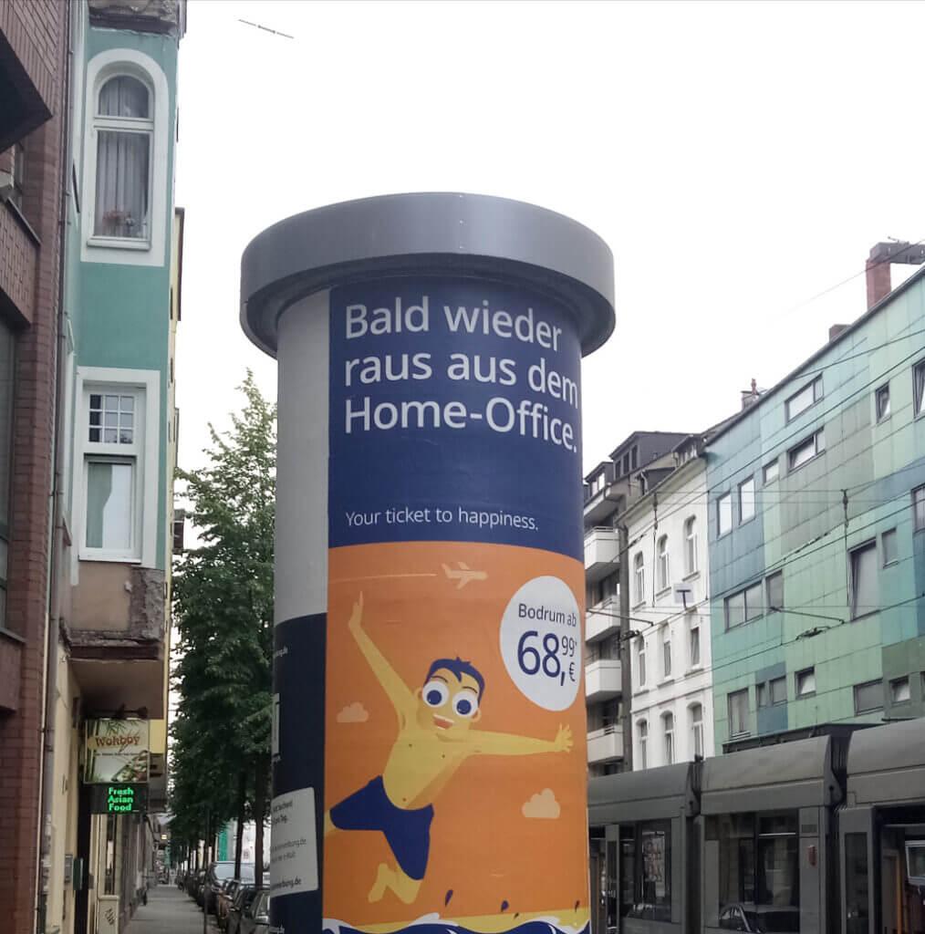 """""""Bald wieder raus aus dem Home-Office"""" Schriftzug auf einer Litfasssäule"""