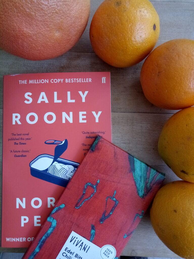 Rotes Cover von Sally Rooney's Normal People mit farblich passender Vivani-Schokolade und Orangen