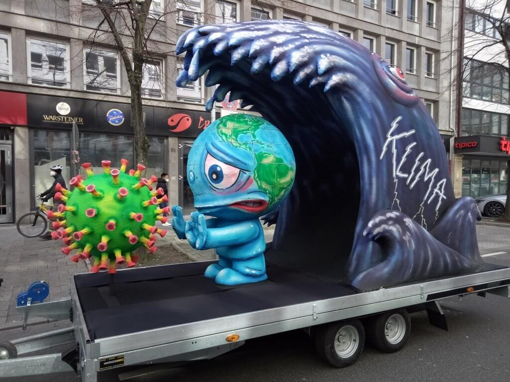 Float depicting earth as a creature trying to fend off the coronavirus before being hit by a tsunami wave of climate crisis